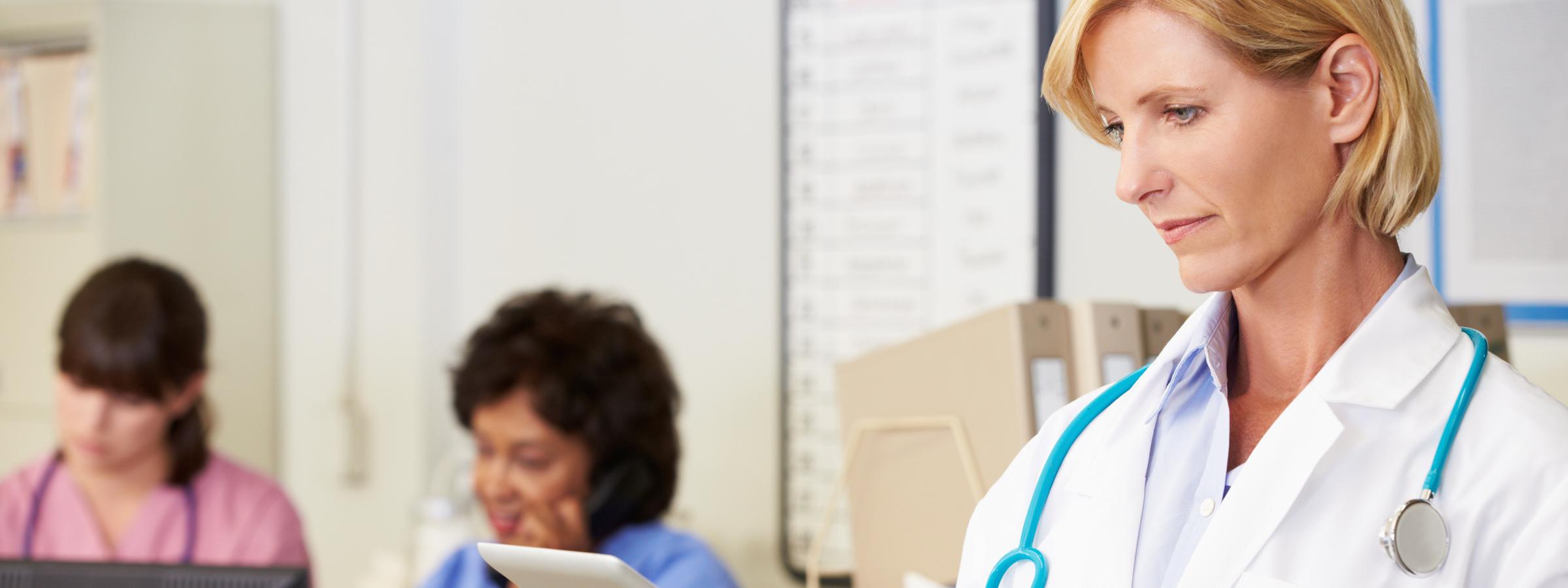 Female Doctor Using Digital Tablet At Nurses Station